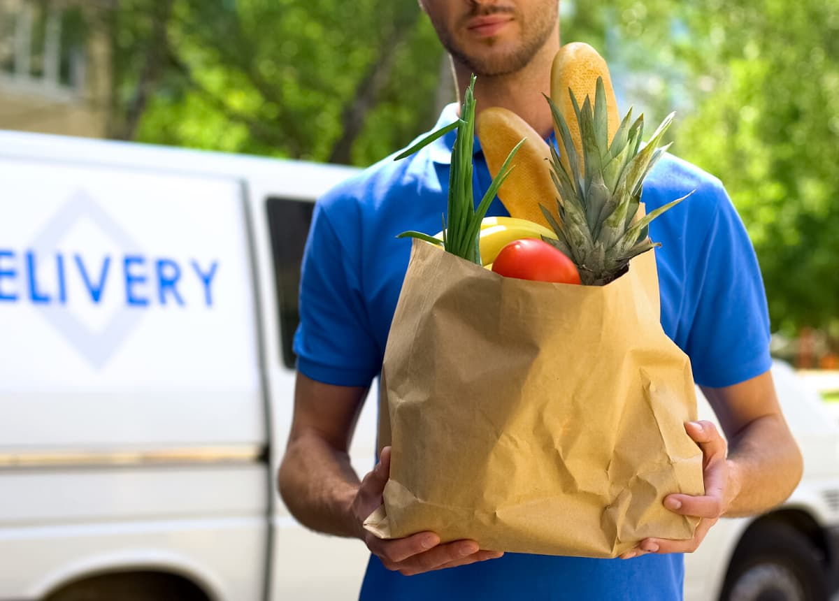 man delivering brown sack of groceries