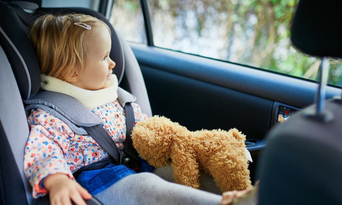 toddler in car seat with teddy bear