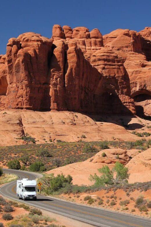 rv driving through red rock canyon