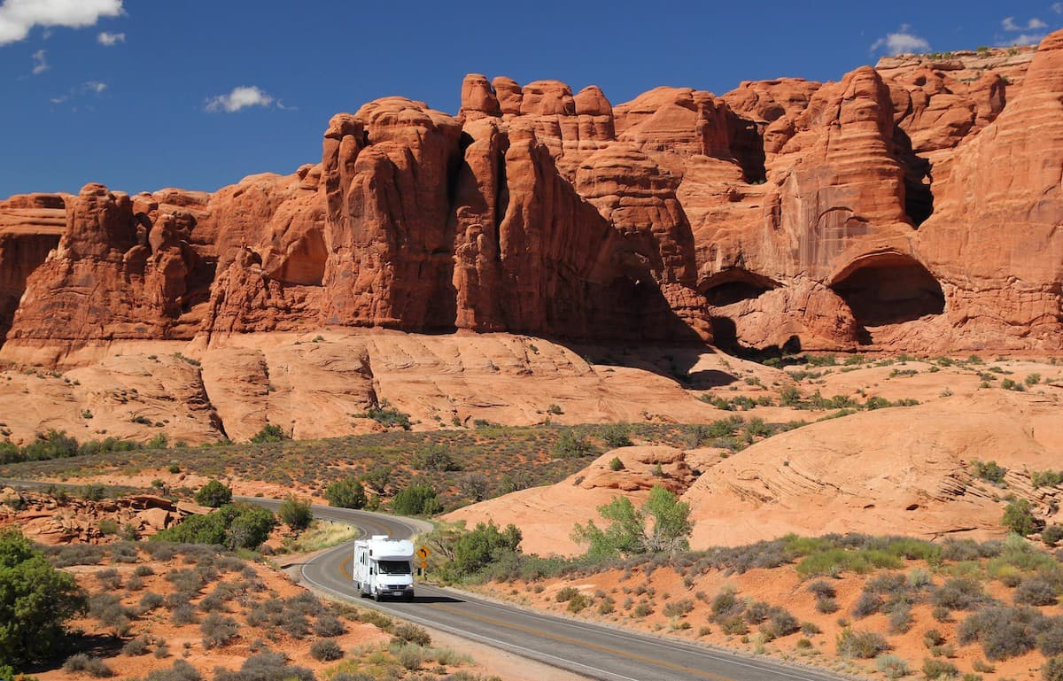 rv driving through red rock canyon