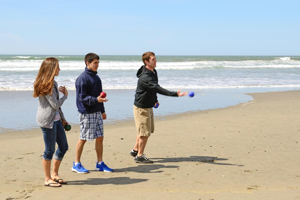 teens on beach playing bocce