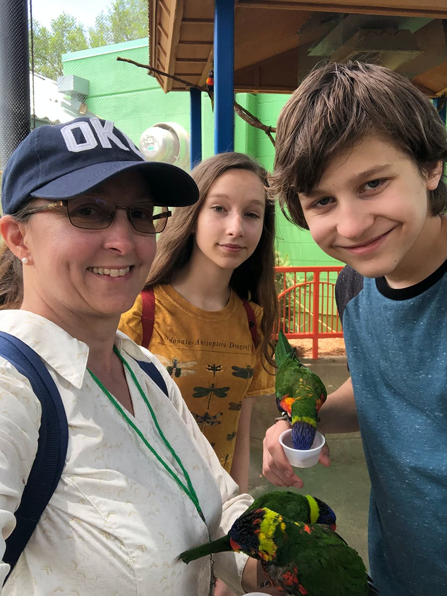 woman and two teens posing with lorikeets