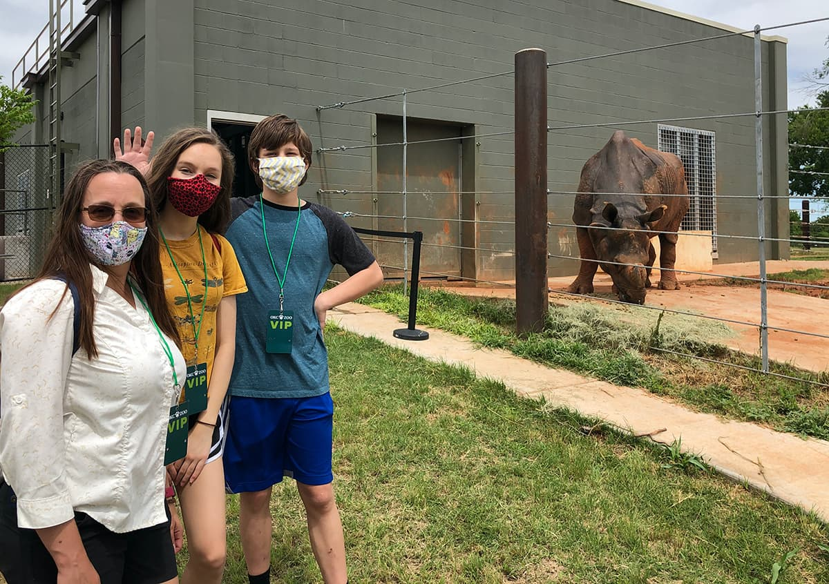 woman and two teens in front of rhinoceros