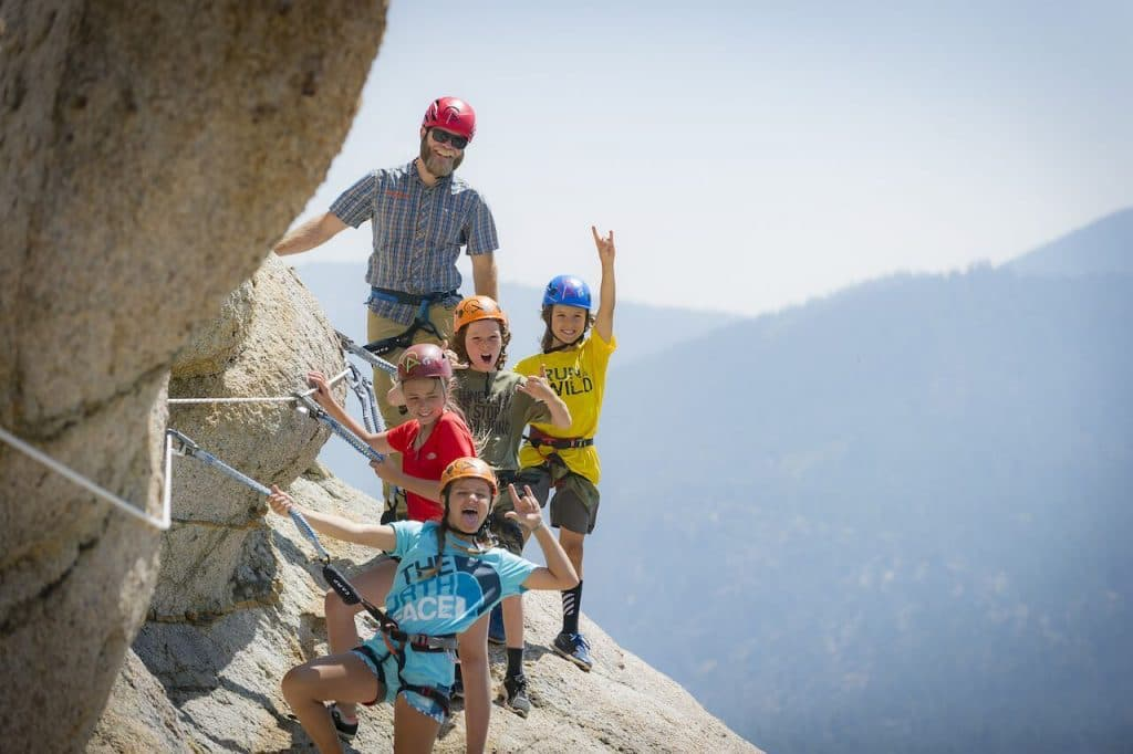 man and children on via Ferrata rock face - Lake Tahoe