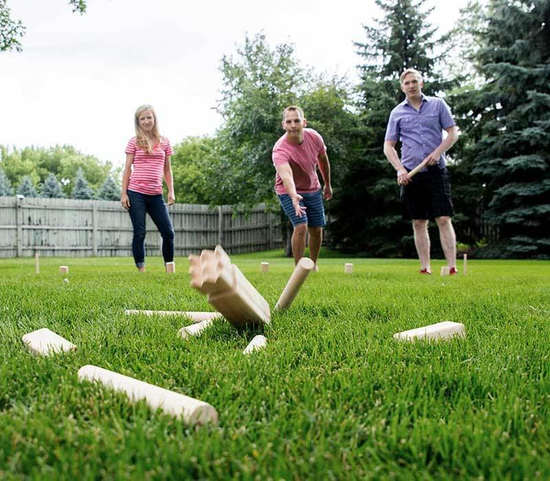 teens and adult playing kubb on lawn