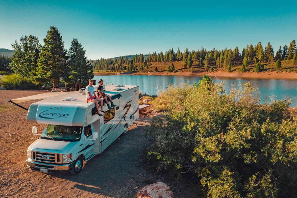 two men atop an RV by a lake