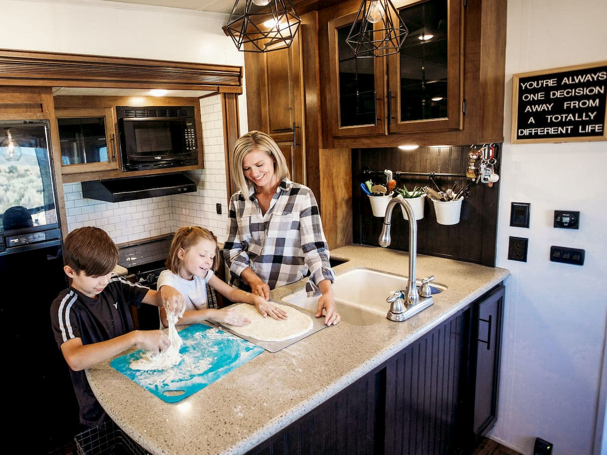 woman and children playig with dough in RV kitchen