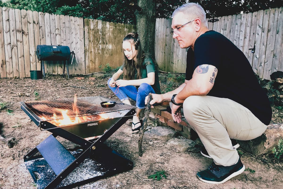 man and girl in front of backyard fire pit