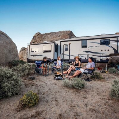 family in front of RV in desert