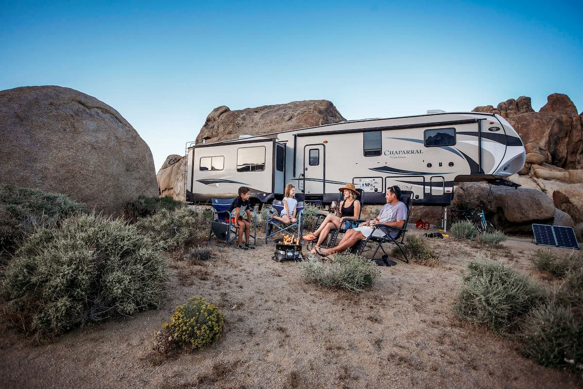 family in front of RV in desert