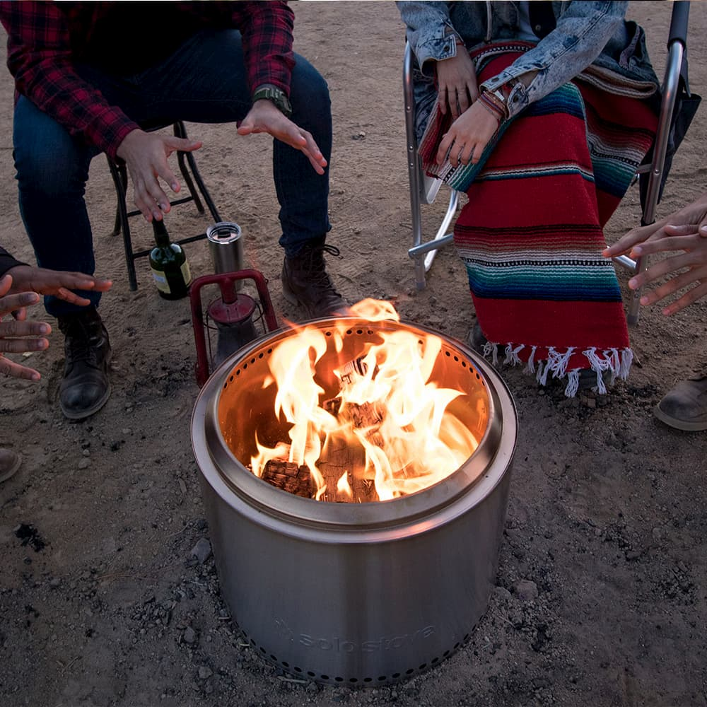 metal campfire fire with fire - campers warming up behind it