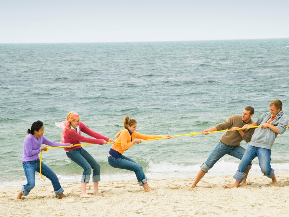 teens playing tug o war on beach