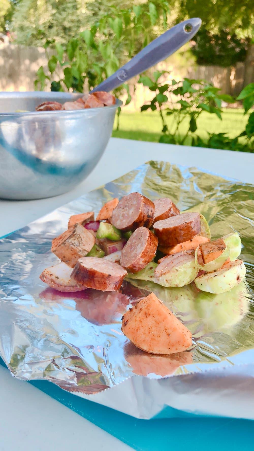 sausage and vegetables on foil sheet