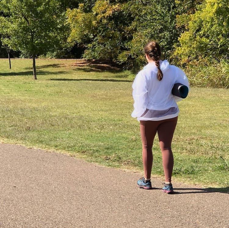 women walking on trail woth yoga mat