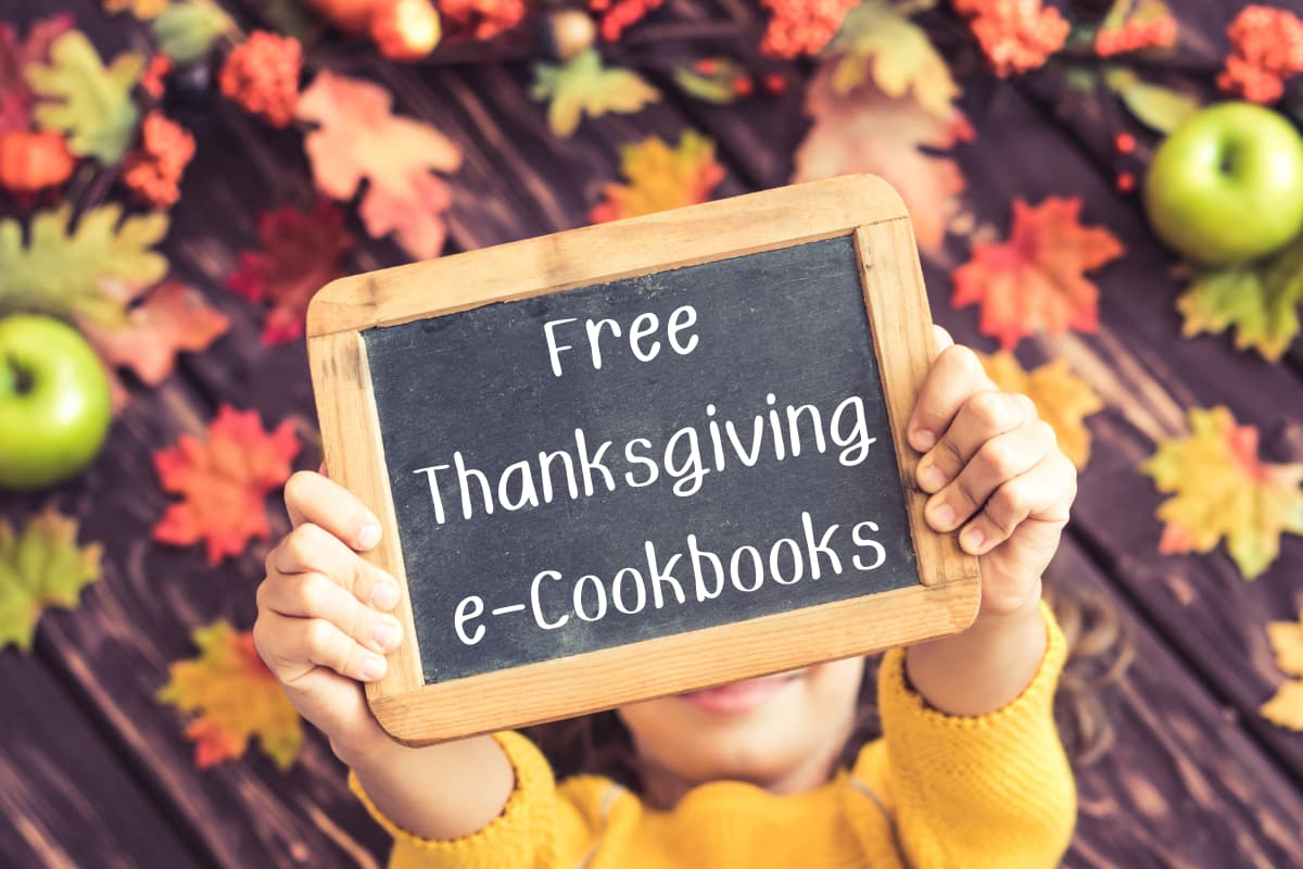 free thanksgiving e-cookbooks on chalk board held by girl with fall behind