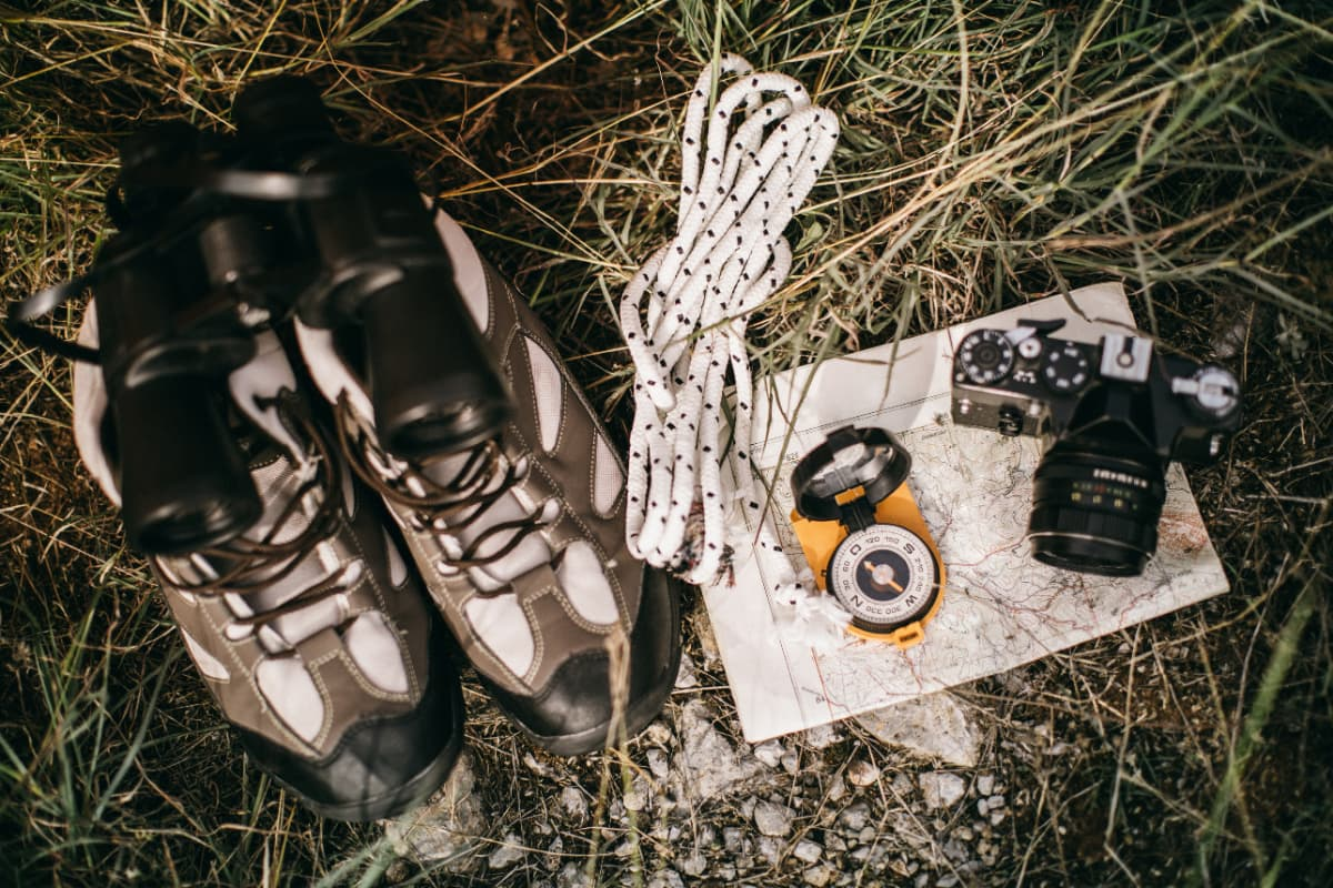 hiking boots, map, camera, ropem and compass