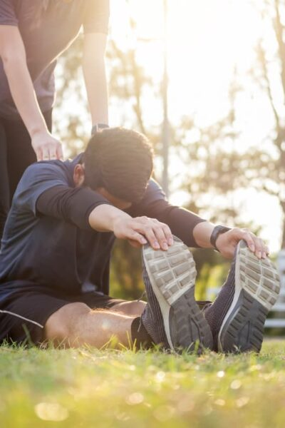 two people stretching in park