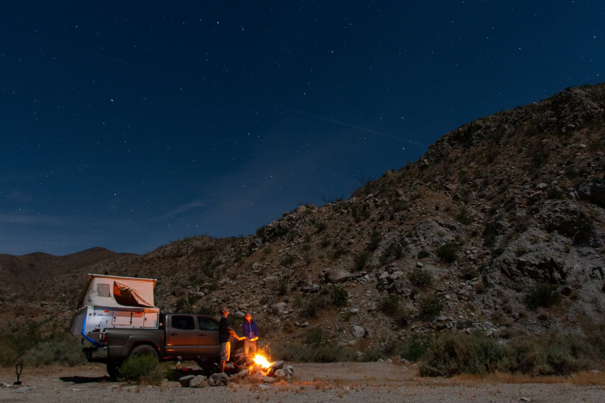overland truck and people by campfire