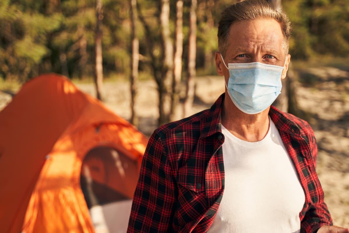 man in mask camping