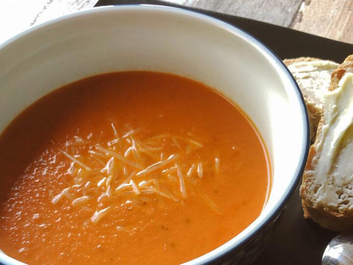 tomato soup in a bowl alongside butter bread