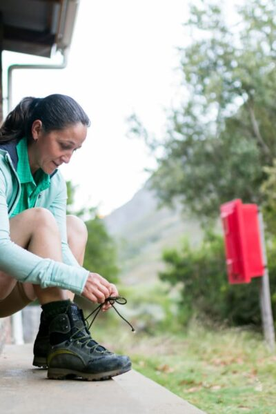 woman tying hiking boots outside