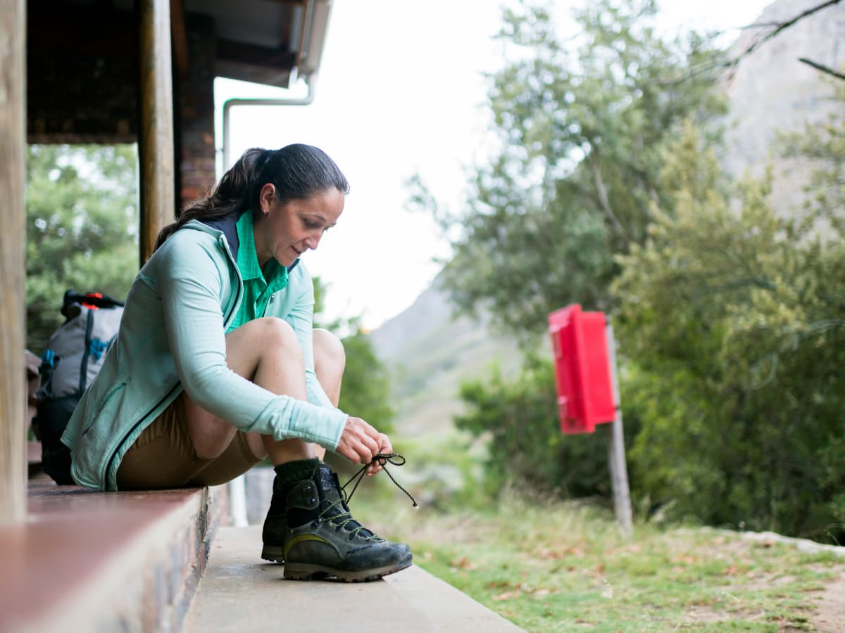 woman tying boots outside