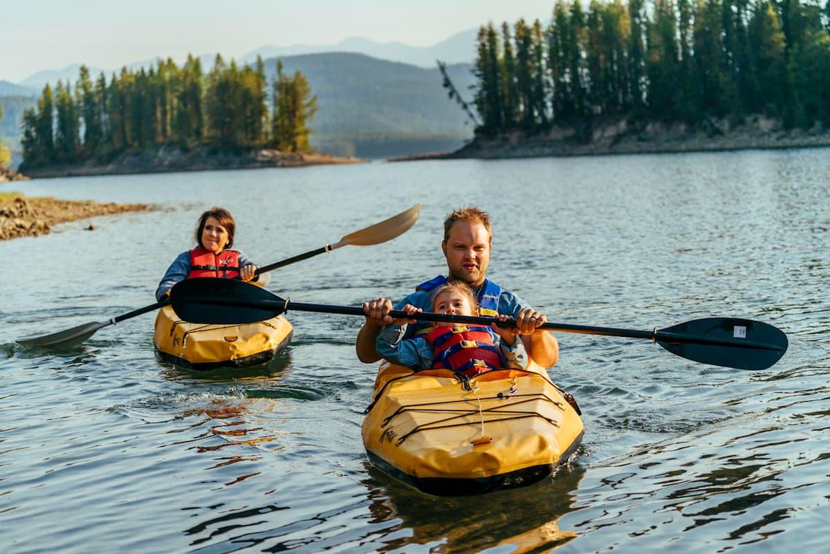 family kayaking, man and child in kayak, natural landscape