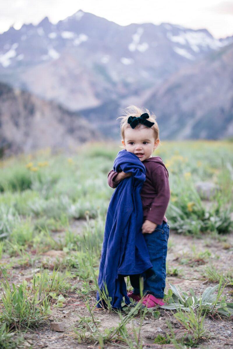 toddler holding blanket outside