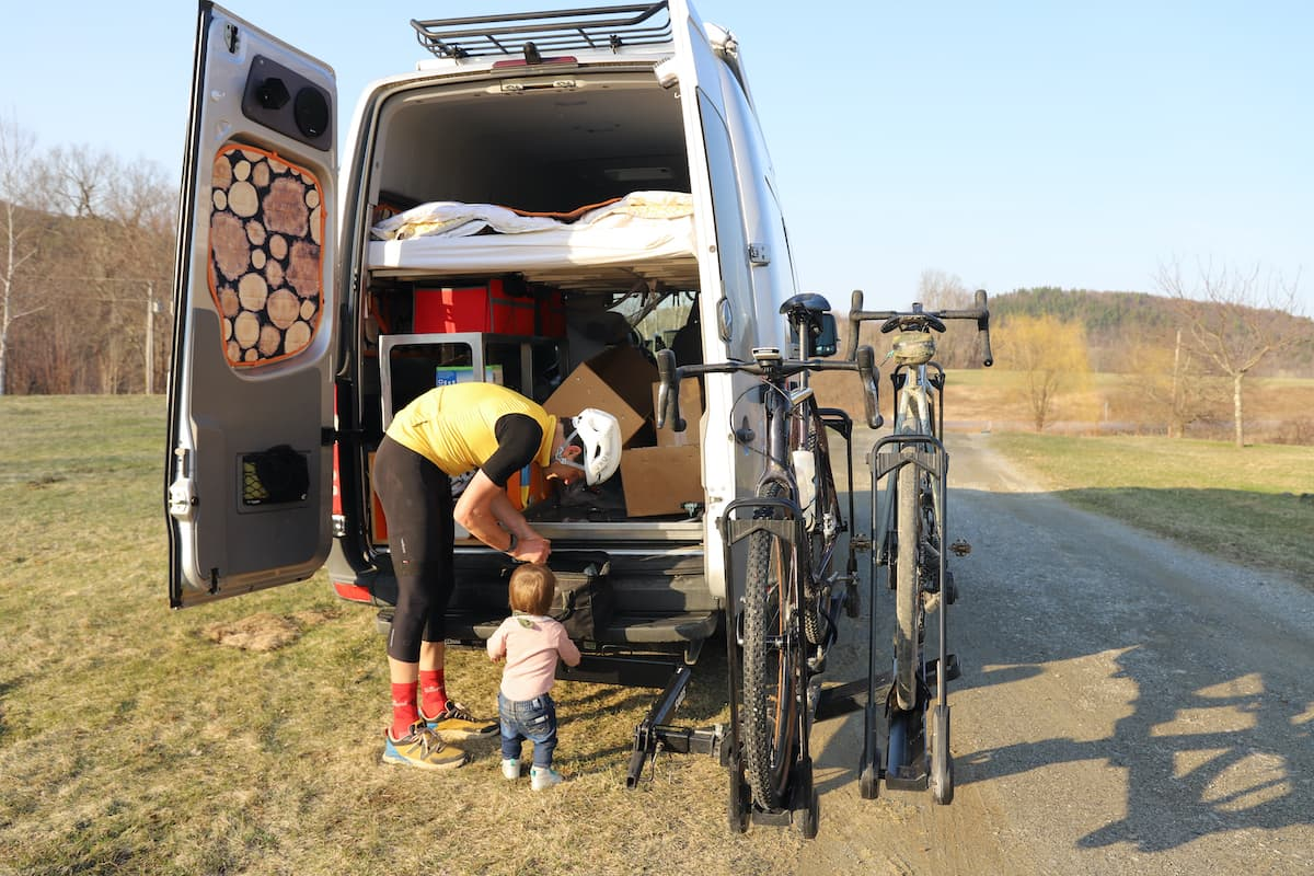man and toddler behind sprinter van, bikes in rack