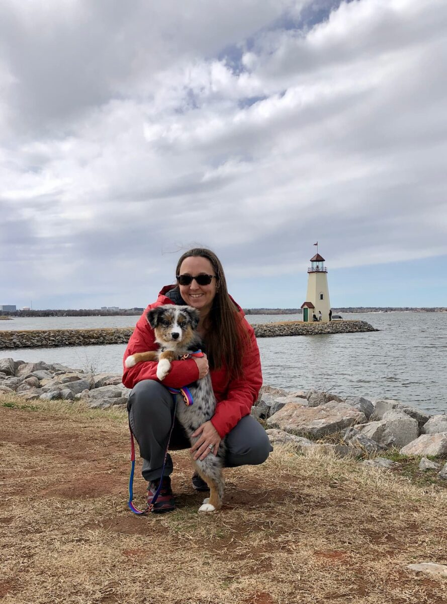 woman with puppy by the lake
