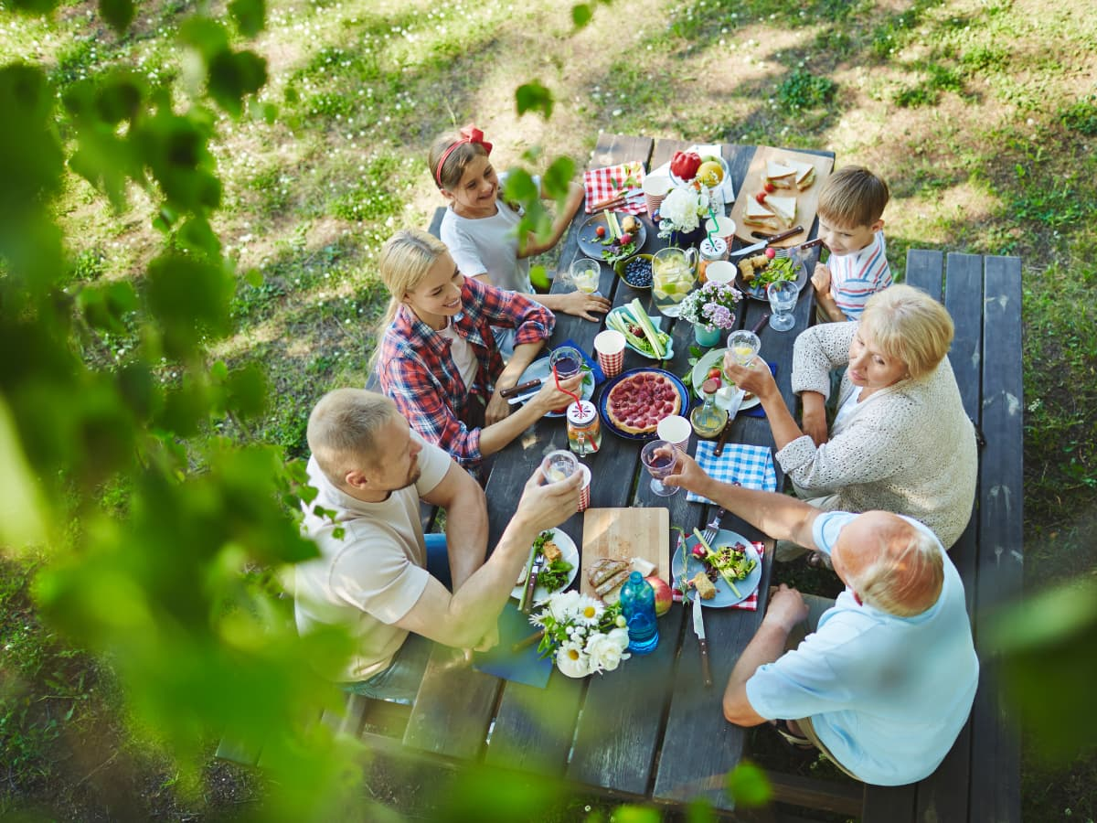 family siting at picnic table for meal