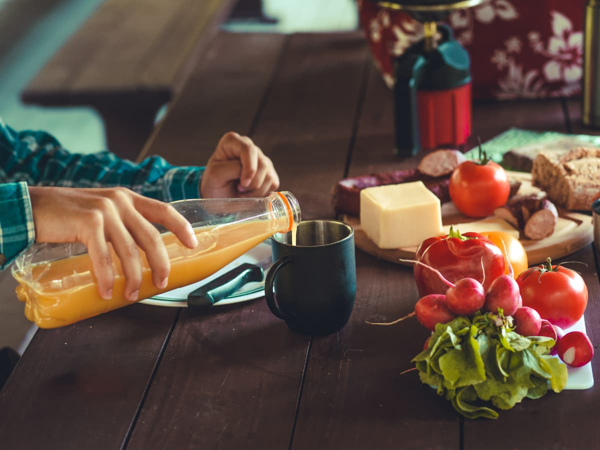 meat and cheese board, person pouring juice in cup
