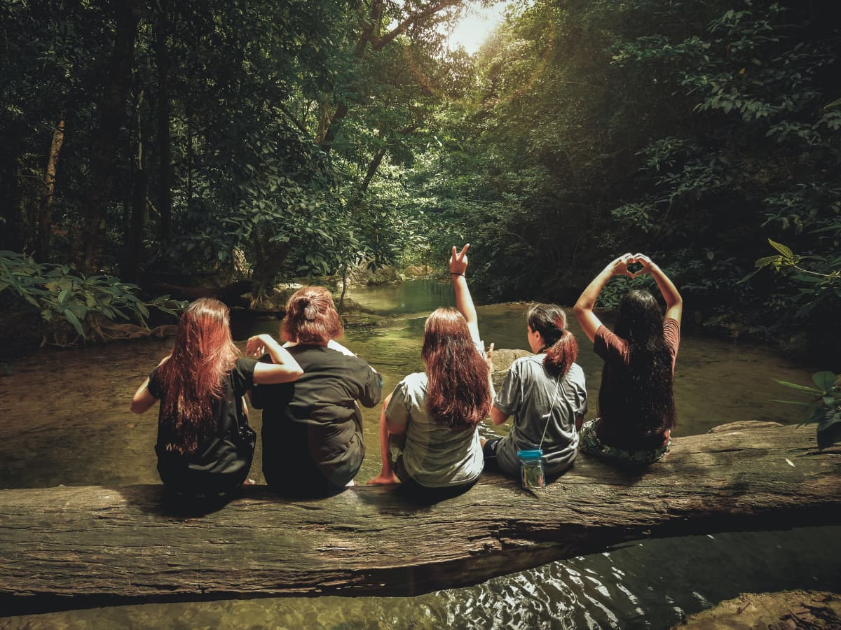 girls on a log over a stream