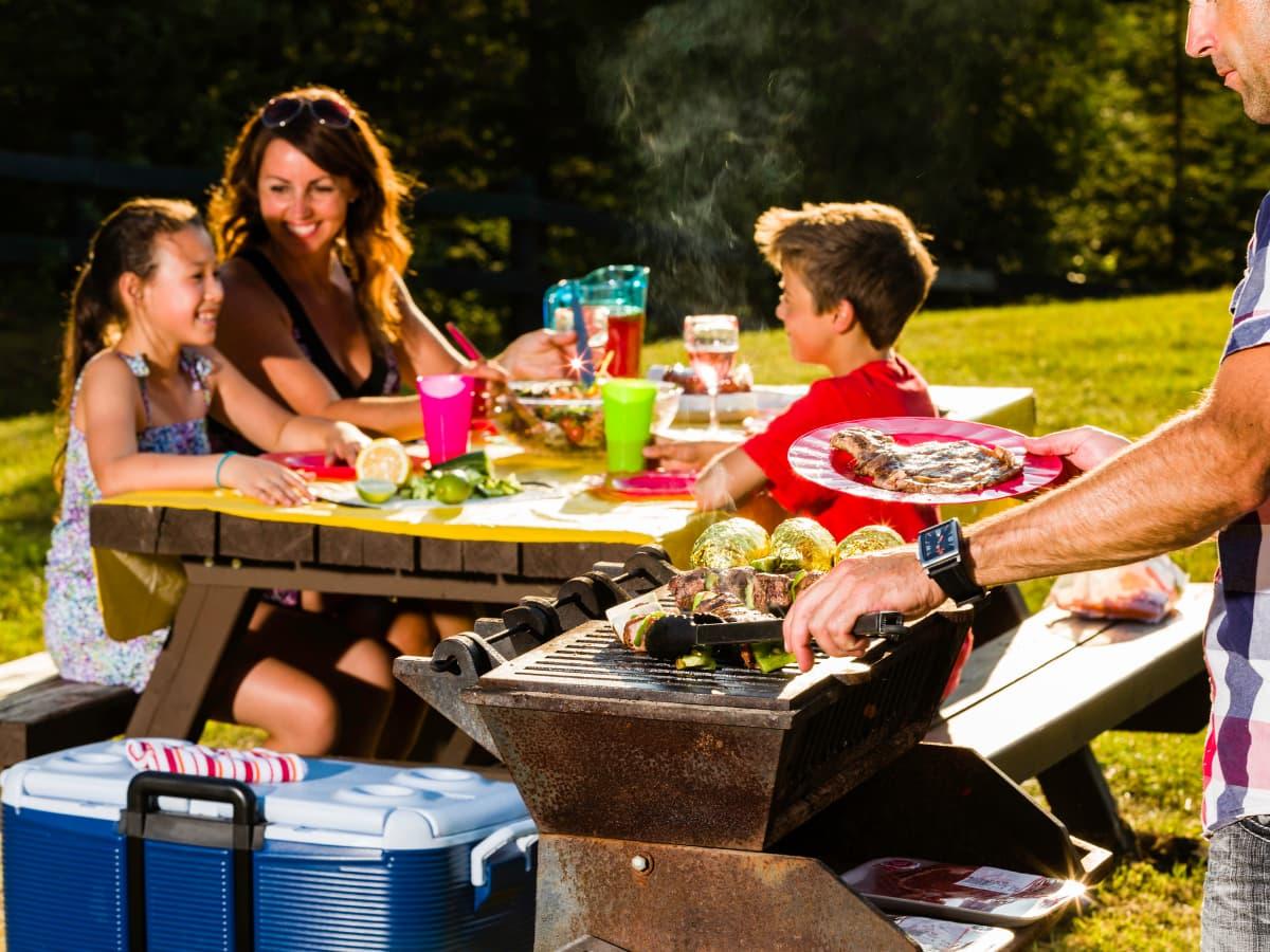 camping family eating bbq at picnic table