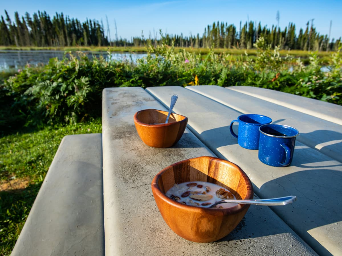 cereal in bowls and coffee on picnic table