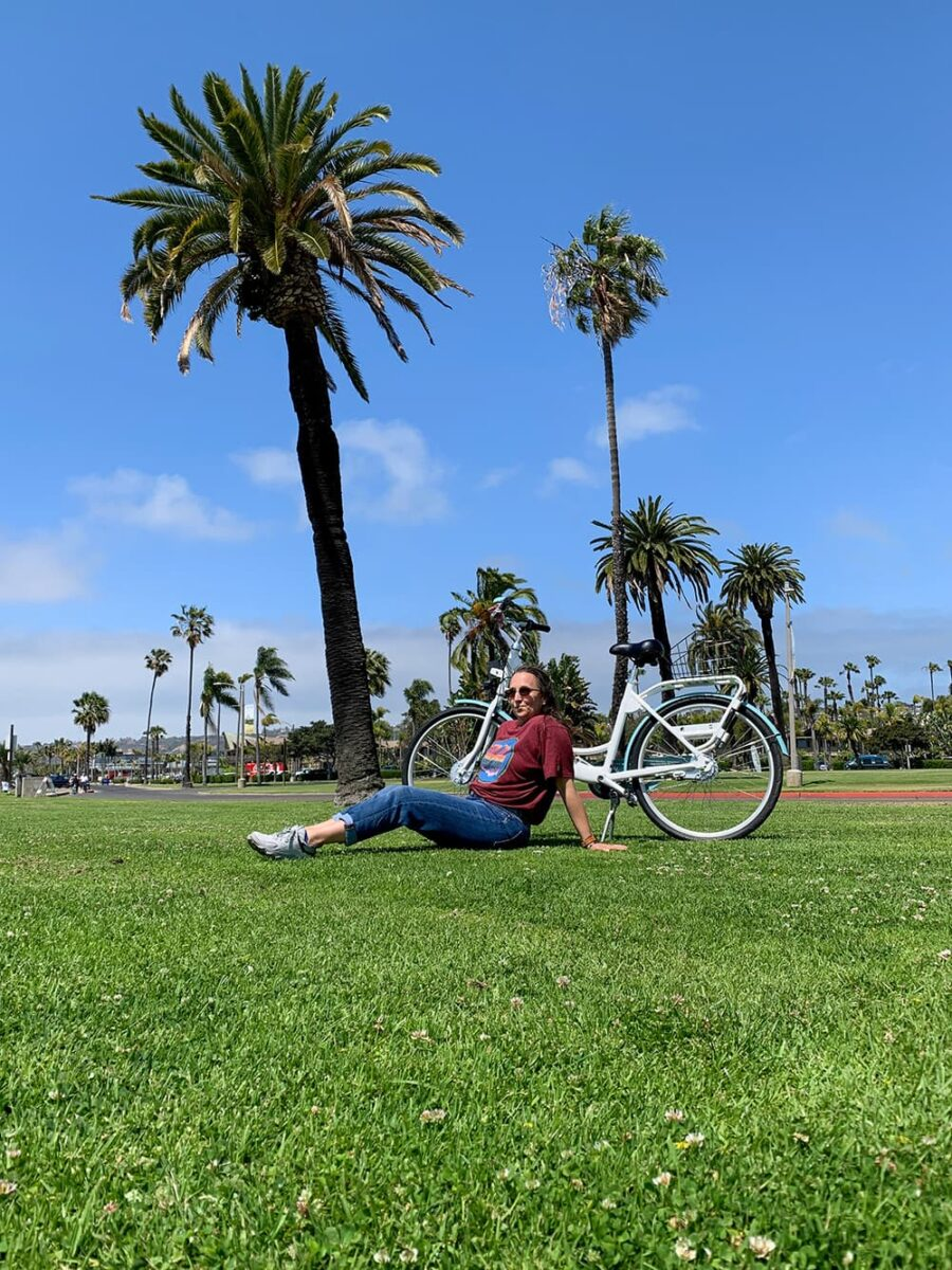 woman sitting on grass in front of bike