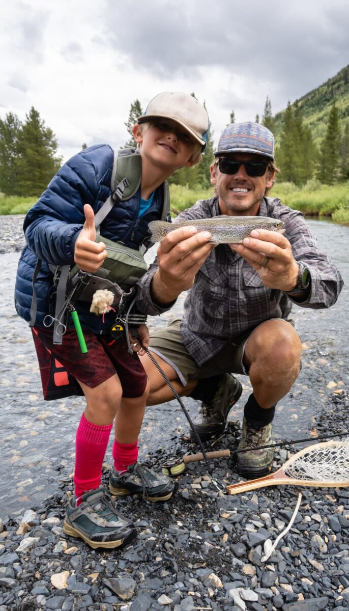 man and boy holding trout they caught