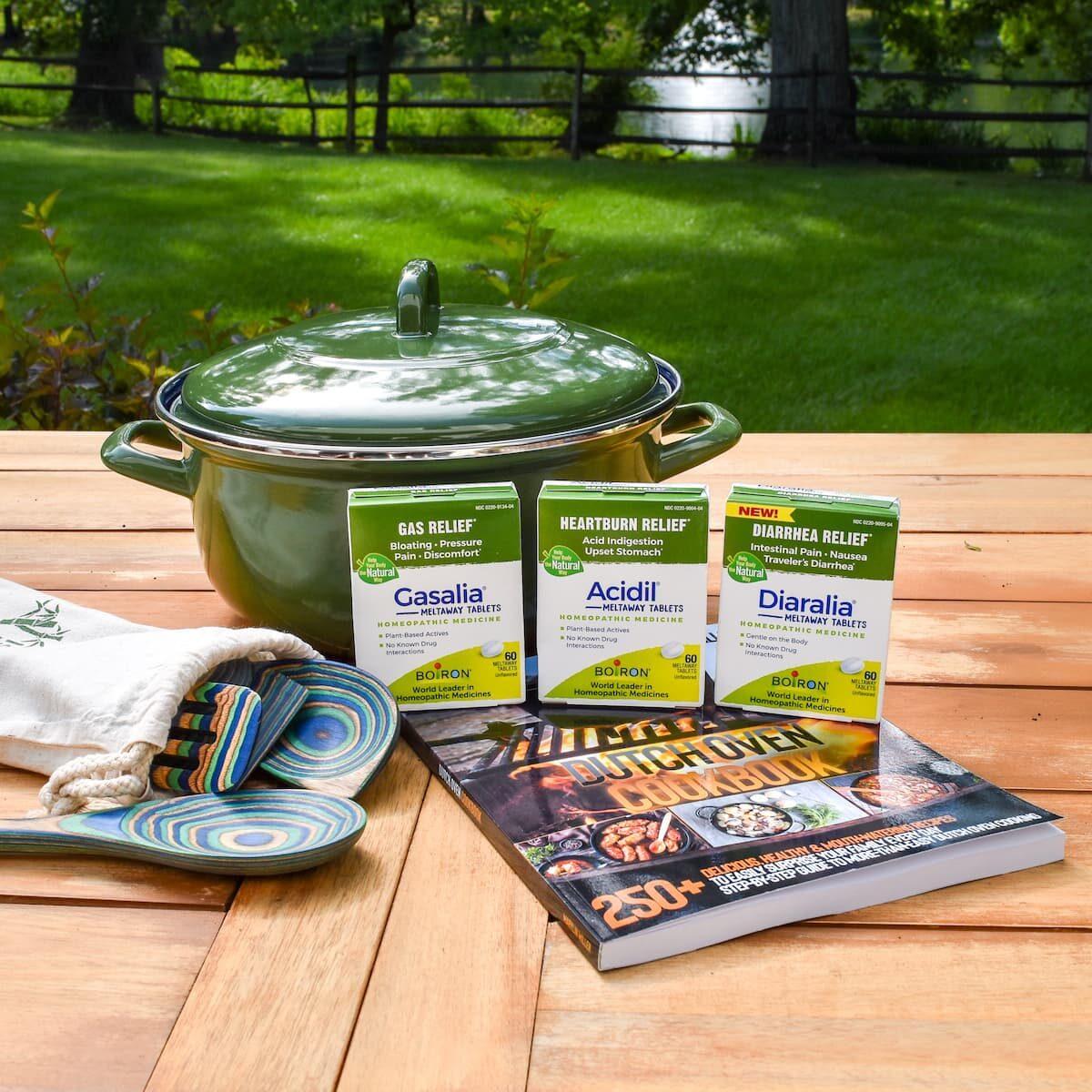 dutch oven, cookbook, utensils, digestive tablets on picnic table