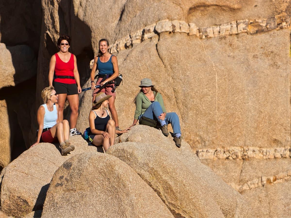 women hiking and sitting on sandstone rocks